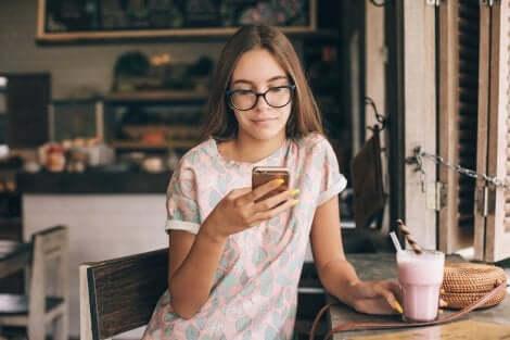 En tenåring som driver med telefonen sin og drikker en smoothie.