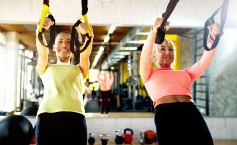 Kvinner som trener på treningsstudioet med slynger.