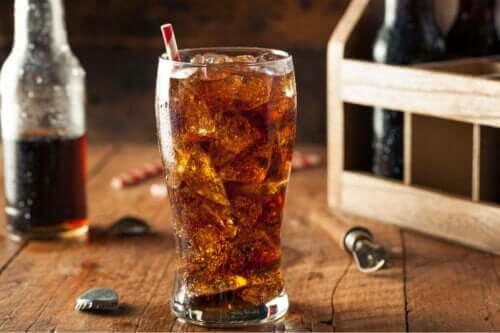 Cola i et glass med flasker i bakgrunnen.