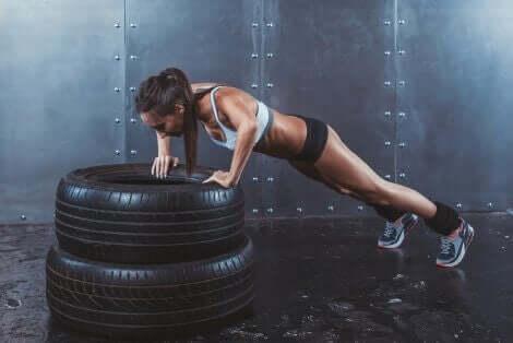 En kvinne som gjør CrossFit-øvelser med dekk