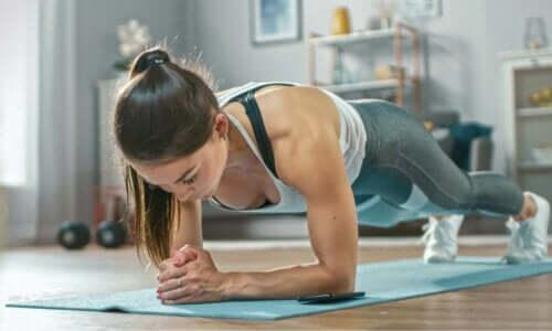 En kvinne som gjør planken som en del av hjemmetreningsrutinen sin.