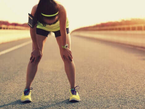 En kvinne som lider av muskeltretthet etter å ha løpt