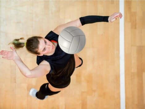 En kvinne som slår ballen på en innebane