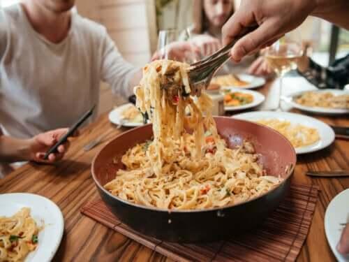 En pastamiddag på et bord med flere personer rundt.