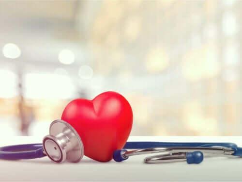 Et hjerte på et bord ved siden av et stetoskop.