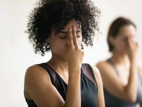 Kvinne med fingrene på pannen, som mediterer for å forbedre pusteteknikken.