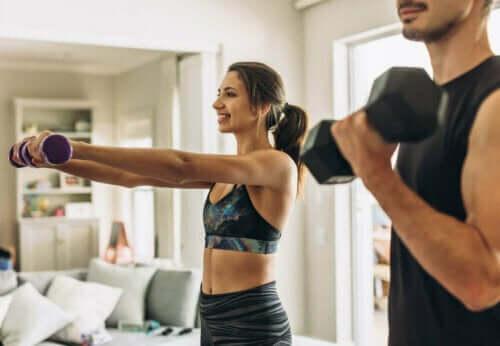Mann og kvinne løfter vekter hjemme.