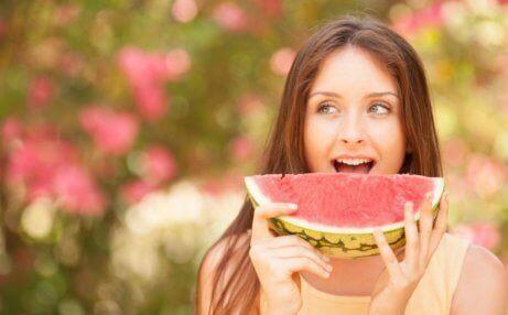 spise frukt før eller etter måltidet? en kvinne som spiser vannmelon