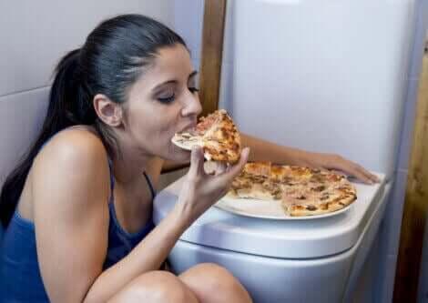 Kvinne gjemmer seg på badet for å spise pizza