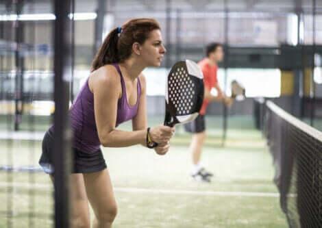 kvinne som spiller paddletennis i ferd med å serve ballen, paddletennis og tennis