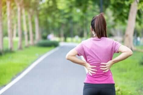 En kvinne som opplever ryggsmerter under trening.