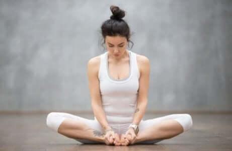 Kvinne som sitter med korslagte ben og gjør hypopressive mageøvelser