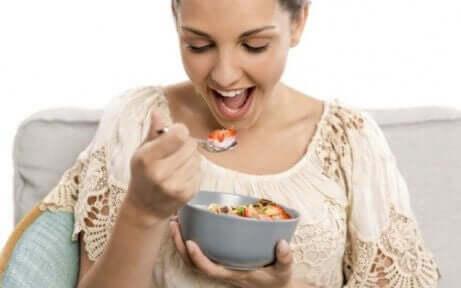 Kvinne som spiser en bolle med fiberrik mat for å gjenopprette tarmfloraen