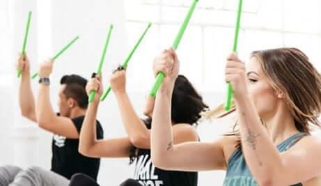 Tre personer som bruker grønne trommestikker for å trene