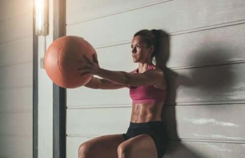 Kvinne som bruker en medisinball for å gjøre knebøy mot veggen