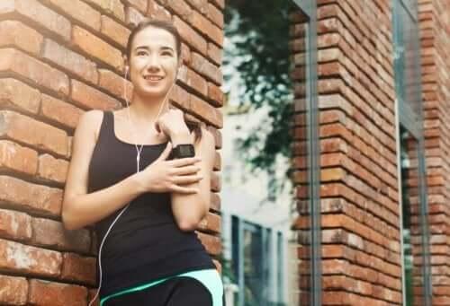 Kvinne som står ved siden av en murbygning og lytter til musikk