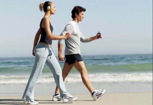 Par som går tur på stranden.