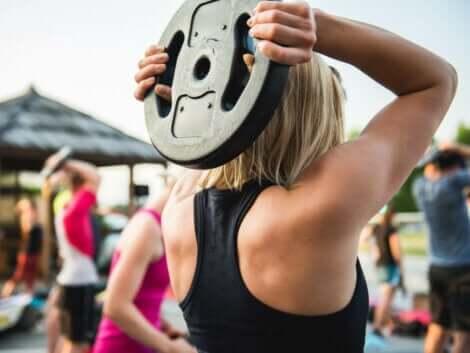En kvinne som holder en vektplate bak hodet.