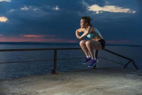 En kvinne som hopper høyt ved stranden