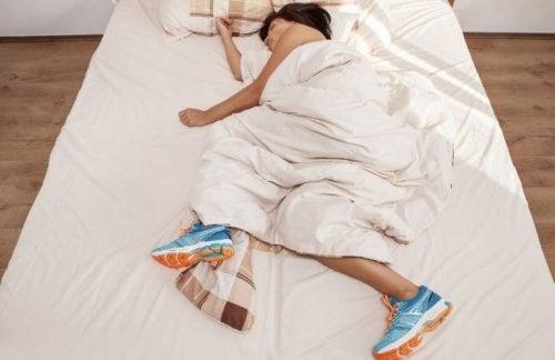 Vrouw in bed met sportschoenen