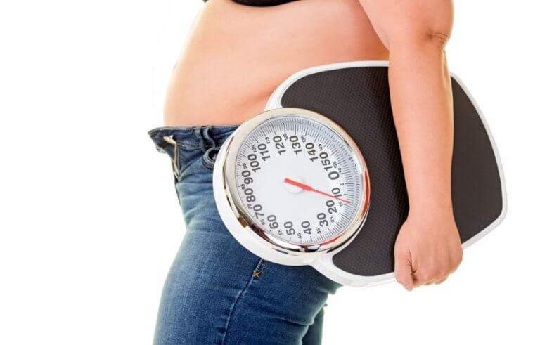 Vrouw met overgewicht houdt een weegschaal vast