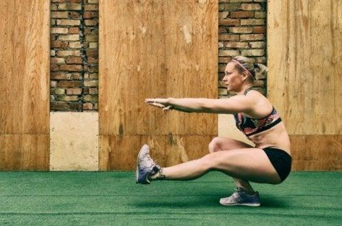 Vrouw doet squat op een been