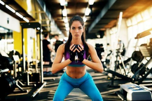 Meisje dat in de sportschool squats