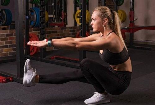 Vrouw die pistol squat doet in de sportschool