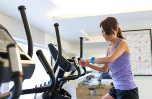 Vrouw op crosstrainer met fitness-horloge