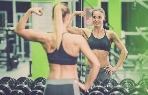 Vrouwen in de spiegel kijkend om haar resultaten te zien van haar bezoek aan de sportschool