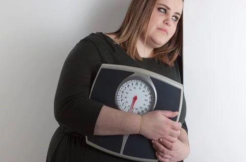 vrouw met overgewicht houdt weegschaal vast