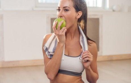 Vrouw eet een appel om duizeligheid te voorkomen