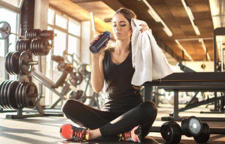 Vrouw drinkt water in de sportschool