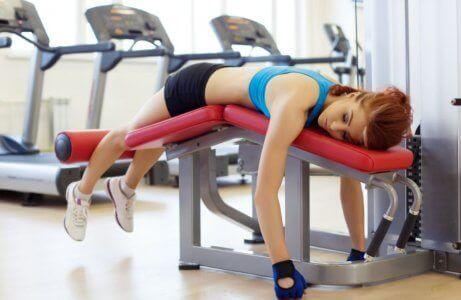 Vrouw ligt op een fitnessapparaat
