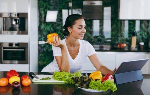 vrouw eet groente achter laptop