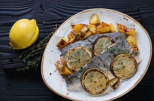 bord met zeebaars en aardappelen en citroen