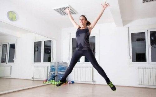 vrouw die jumping-jacks en cardio-oefeningen doet
