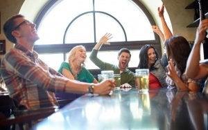 mensen aan een tafel drinken bier en hebben dolle pret