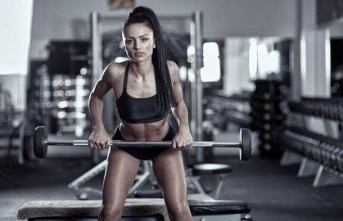 Vrouw doet barbell row in sportschool