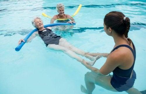 twee oudere vrouwen krijgen zwemles in zwembad