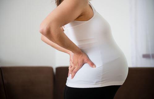 zwangere vrouw met handen in de rug heeft rugpijn
