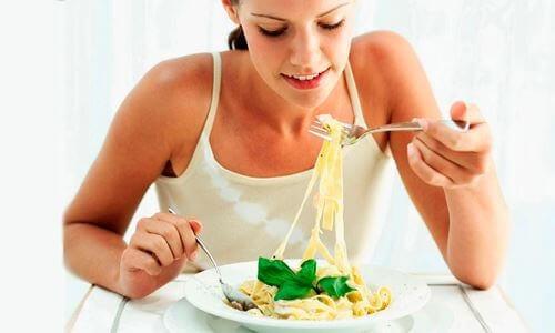jonge vrouw eet bord met pasta