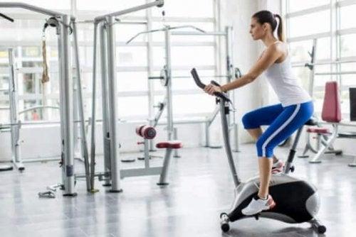 vrouw zit op hometrainer in sportschool