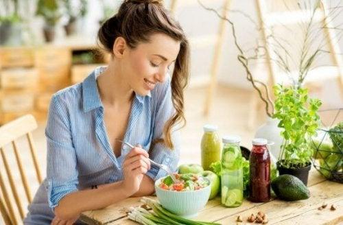 vrouw zit aan tafel te eten