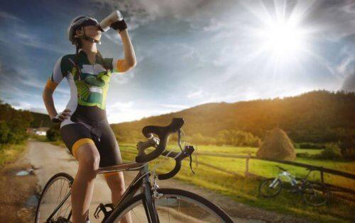 Vrouw die op haar fiets uit haar bidon drinkt