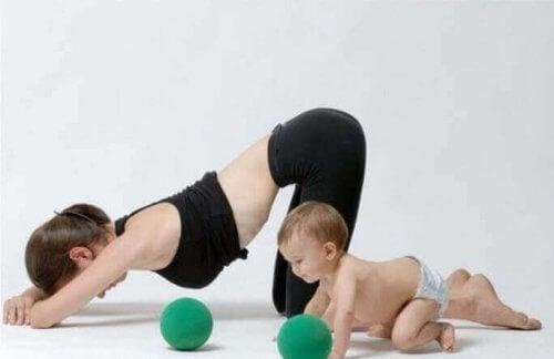 Vrouw doet yoga naast haar zoontje postpartum-oefeningen