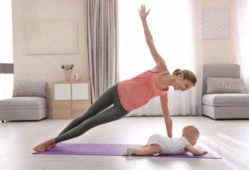 Moeder die yoga doet naast haar baby.