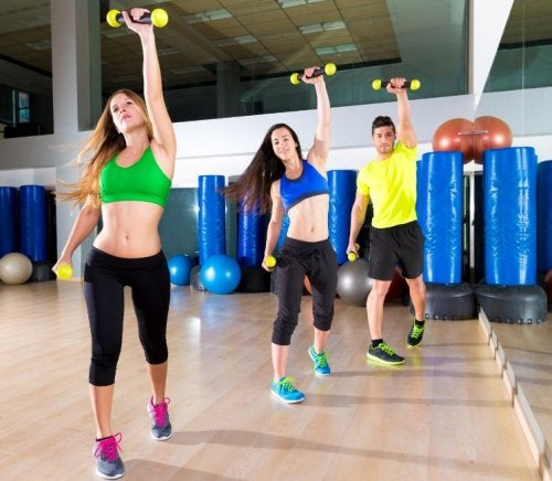 Trzy osoby ćwiczą z ciężarkami