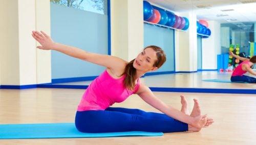 kobieta w różowym topie, siedząca na macie i ćwicząca pilates