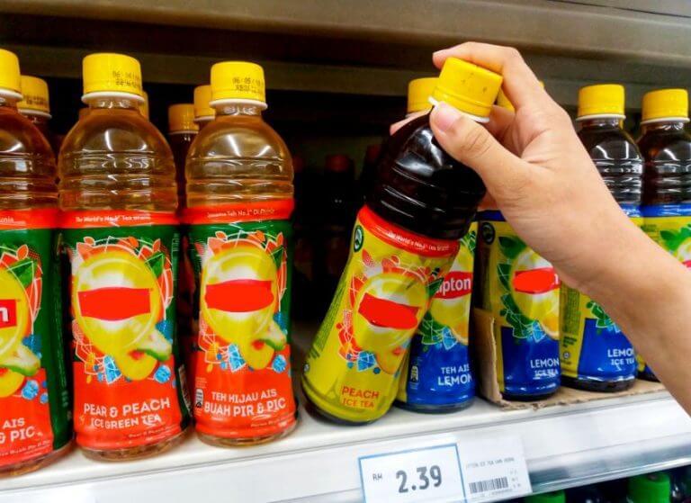 Dłoń sięgająca po napój w butelce z półki sklepowej - niezdrowe jedzenie, którego należy unikać
